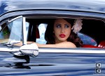 strolling pinup model posing in streamlined custom car