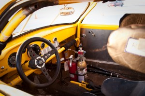 A shot of the Ghia's interior with cage, fire extinguisher, race bucket and aluminum door panels